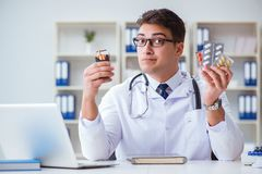 The male doctor in anti-smoking conceptwithcigarette pack. Male doctor in anti-smoking conceptwithcigarette pack Stock Images