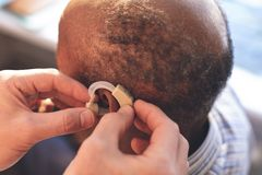 Male doctor applying hearing aid to senior man ear. Hight angle view of caucasian male doctor applying hearing aid to African senior men ear in clinic stock photos