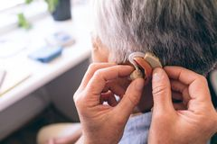 Male doctor applying hearing aid to senior woman. Middle section of Caucasian male doctor applying hearing aid to senior mixed race woman ear in clinic at royalty free stock photos