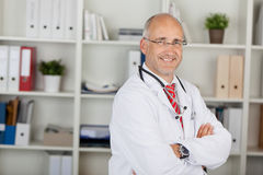 Male Doctor With Arms Crossed Standing Against Shelves. Portrait of confident mature male doctor with arms crossed standing against shelves in clinic Stock Photos
