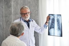 Male doctor and Asian patient are examining x-ray film together. Senior Male doctor and Asian patient are examining x-ray film in a medical room together stock image