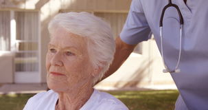 Male doctor assisting senior woman on wheelchair in the backyard stock footage
