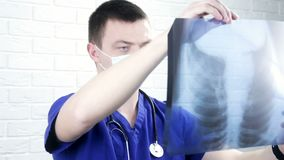 Male doctor in blue coat looking the x-ray picture of lungs in his office.
