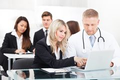 Male doctor and businesswoman with laptop Stock Images