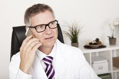 Male Doctor Calling Someone Using Phone Royalty Free Stock Photos