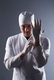 Male doctor in cap with beard wear rubber medical gloves in cont Stock Images