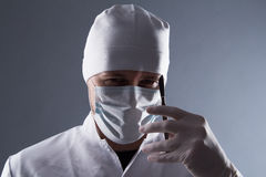 Male doctor in cap, mask and rubber medical gloves holding scalp Royalty Free Stock Photography