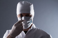 Male doctor in cap, mask and rubber medical gloves holding scalp. El Royalty Free Stock Photography
