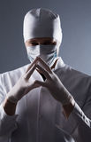 Male doctor in cap and mask wear rubber medical gloves in contra Stock Photo