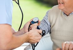 Male Doctor Checking Blood Pressure Of Senior Man Royalty Free Stock Photo