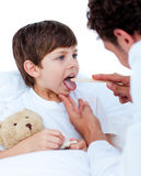 Male doctor checking little boy's throat Royalty Free Stock Images