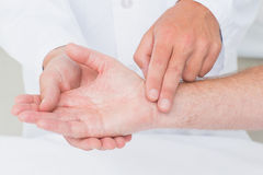 Male doctor checking patients pulse. Cropped image of male doctor checking patients pulse rate in clinic Royalty Free Stock Photography