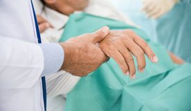 Male doctor is checking a senior man patient pulse. Close up on hands. Male doctor is checking a senior man patient pulse in a medical room. Health care Royalty Free Stock Photos