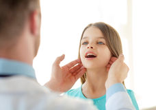 Male doctor checks little girl lymph nodes Royalty Free Stock Image