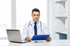 Male doctor with clipboard and laptop in office Royalty Free Stock Photos