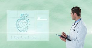 Male doctor with clipboard looking at human heart on interface graphics. Digital composite of Male doctor with clipboard looking at human heart on interface Royalty Free Stock Image
