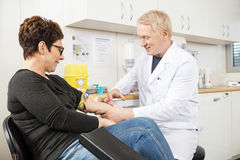 Male Doctor Collecting Patient's Blood For Test. Mature male doctor collecting patient's blood for test in clinic royalty free stock images
