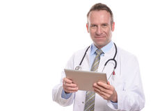 Male doctor consulting a tablet computer. Professional male doctor in a white coat standing consulting a tablet computer reading the information with a friendly Stock Photography