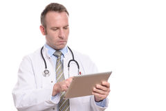 Male doctor consulting a tablet computer. Professional male doctor in a white coat standing consulting a tablet computer reading the information with a serious Royalty Free Stock Photography