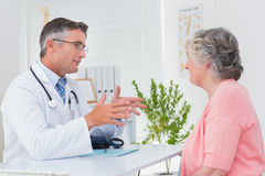Male doctor conversing with female patient at table Royalty Free Stock Image
