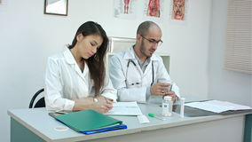 Male doctor counting money and giving it to his female partner stock video footage