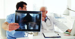 Male doctor and coworker examining x-ray
