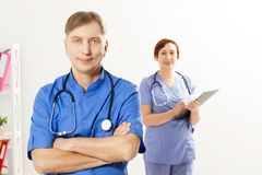 Male doctor with crossed arms and female doctor with folder in medical office, medical insurance, copy space, selective focus stock photography