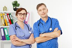 Male doctor with crossed arms and female doctor in medical office, medical insurance, copy space, selective focus royalty free stock photo