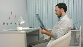 Male doctor or dentist looking at x-ray. People stock video