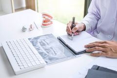 Male doctor or dentist writing report working with tooth x-ray f stock photography