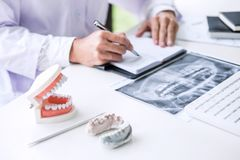 Male doctor or dentist writing report working with tooth x-ray film, model and equipment used in the treatment of dental and stock images