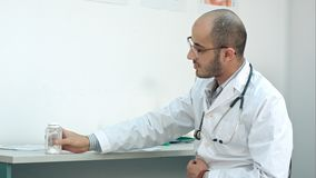 Male doctor describing diagnosis and showing bottle of pills to his patient. Professional shot on BMCC RAW with high dynamic range. You can use it e.g. in your stock image