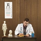 Male doctor at desk writing. Royalty Free Stock Photo