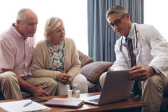 Male doctor discussing over laptop with senior couple at retirement home. Front view of confident male doctor discussing over laptop with senior Caucasian couple stock photography