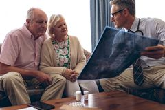 Male doctor discussing over x ray with senior couple royalty free stock photo