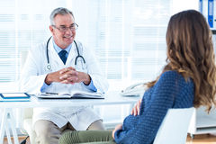 Male doctor discussing with pregnant woman in clinic Stock Photography
