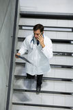 Male doctor discussing x-ray on mobile phone while walking downstairs Stock Photo
