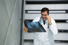 Male doctor discussing x-ray on mobile phone while walking downstairs Royalty Free Stock Images