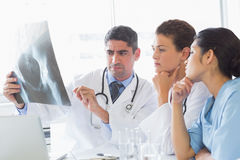 Male doctor discussing xray with colleagues Stock Photography