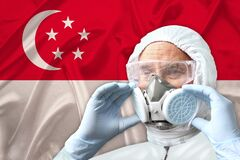 Male doctor, disinfector in a protective suit, respirator, glasses on the background of the Singapore national silk flag, the