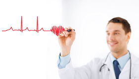 Male doctor drawing heart in the air. Medicine, health and hospital concept - male doctor drawing heart and cardiogram in the air with marker Stock Image