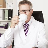 Male doctor drinking a cup of tea or coffee Stock Photos
