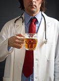 Doctor is drinking beer Royalty Free Stock Photos