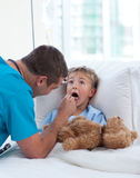 Male doctor examining child throat Stock Photo