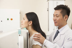 Male Doctor Examining Female Patient's Mid Section With X-ray Machine Royalty Free Stock Image