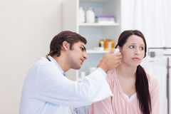 Male doctor examining his patients ear Royalty Free Stock Image