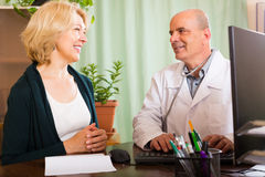 Male doctor examining  mature female patient Royalty Free Stock Photos