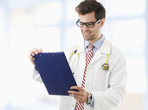 Male doctor examining medical report Stock Photos