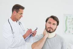 Male doctor examining a patients sprained neck Royalty Free Stock Image