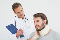 Male doctor examining a patients sprained neck Royalty Free Stock Photography